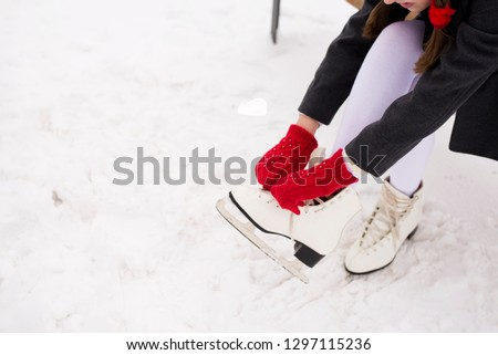 girl puts on white figure skates in the park #1297115236