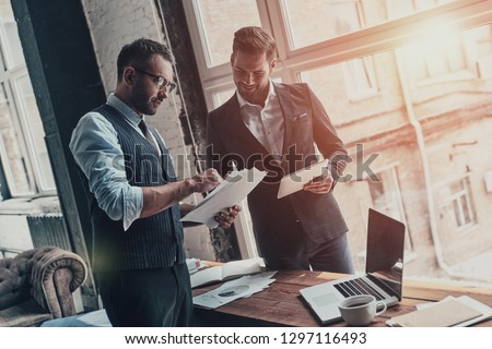 Team of innovators. Two young modern men in formalwear working together while standing indoors #1297116493