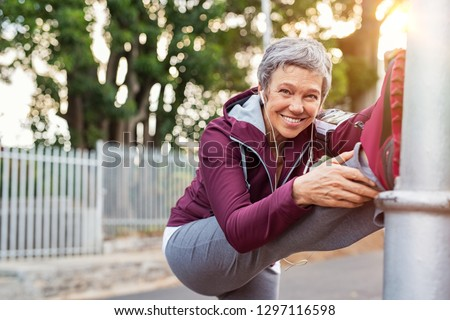 Smiling retired woman listening to music while stretching legs outdoors. Senior woman enjoying daily routine warming up before running. Sporty lady doing leg stretches and looking at camera. #1297116598