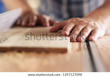 Hands of a real woodworker sawing a piece of wood with a table saw in woodworking studio #1297127098