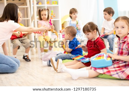 Teacher and cute children during music lesson in preschool #1297180735