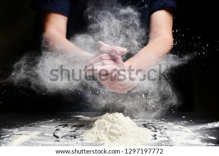 Cook slams splash hands with flour. White dust cloud of flour #1297197772