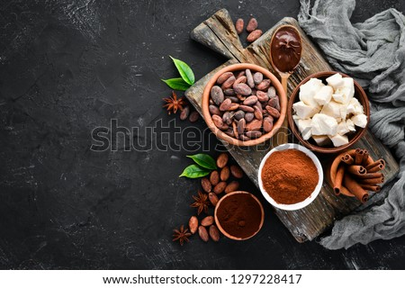 Cocoa beans, chocolate, cocoa butter and cocoa powder on a black background. Top view. Free copy space. #1297228417