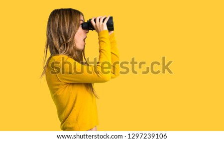 young girl with yellow sweater and looking in the distance with binoculars on isolated yellow background Royalty-Free Stock Photo #1297239106