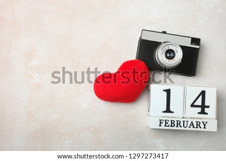 Calendar with date of February 14, old retro camera and red soft heart on neutral background. Concept Valentine's day. Copy space, top view.