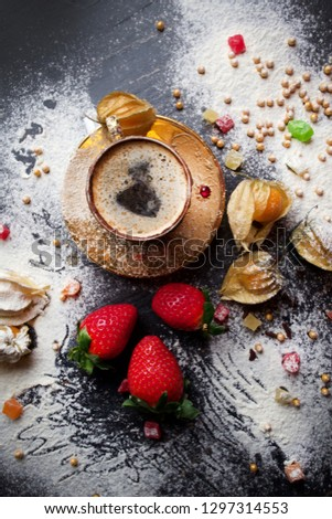 Golden cup of coffee with sweets and berries Royalty-Free Stock Photo #1297314553