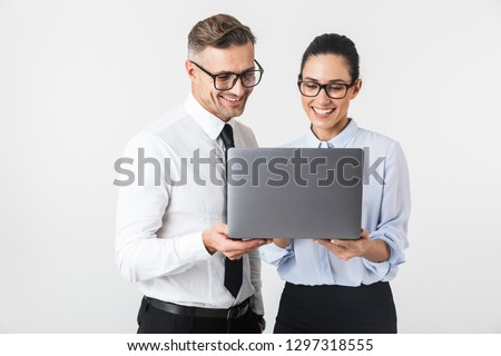 Image of young business colleagues couple isolated over white wall background using laptop computer.