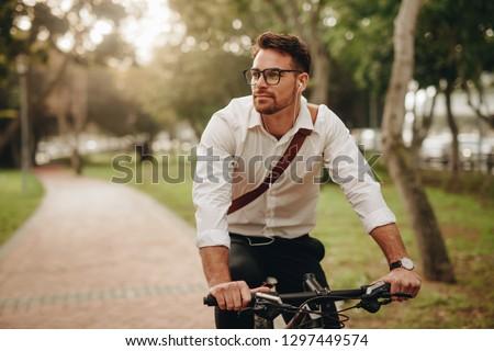 Man enjoying music using earphones while commuting to office on a bicycle. Businessman biking to office while listening to music. #1297449574
