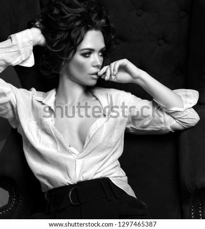 Beautiful sensual curly hair woman posing in white man shirt sitting in armchair looking at the corner. Black and white image