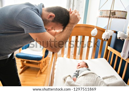 Tired father with Upset Baby Suffering with Post Natal Depression. Royalty-Free Stock Photo #1297511869