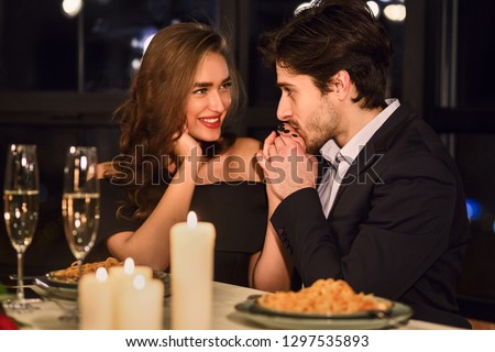 Handsome man kissing hand of his girlfriend in restaurant during romantic dinner #1297535893
