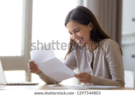 Happy excited woman student customer reading letter with good news, great cheap offer, get job opportunity, scholarship admission, loan approval, money refund holding paper mail bank statement Royalty-Free Stock Photo #1297544803