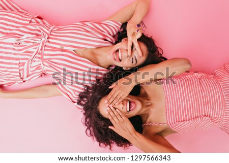 Photos in studio of two young and chatming girls in beautiful dress and bright striped sundress, smiling and closing their eyes from camera flashes #1297566343