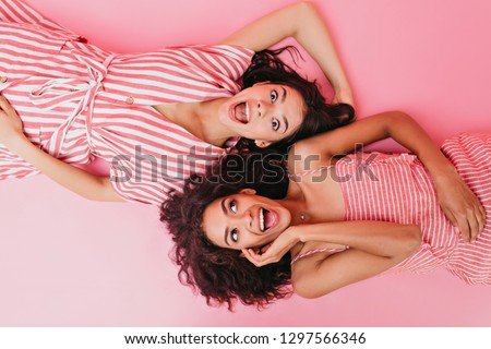 On isolated background two dark-skinned girls with beautiful hair and surprised faces pose for camera while lying on their backs #1297566346