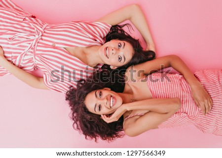 Portrait on isolated pink background in studio of young girls enjoying photo shoot. Ladies in stripped outfits laughing #1297566349