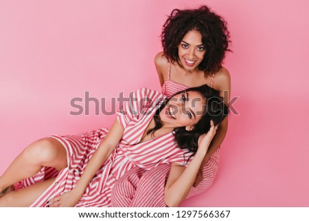 Beautiful girls posing in good mood and having fun on isolated pink background #1297566367