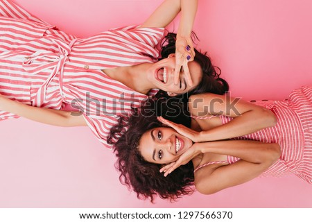On pink isolated background beautiful dark-skinned girls with cute smiles are having fun and posing in front of camera lying on their backs #1297566370