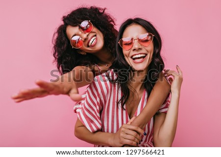 Unrestrained merriment of two girls captured on snapshot. Photos in pink shades of brunettes with beautiful curls, embracing in friendly way #1297566421