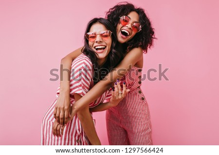 African sisters with dark curls are having fun in wonderful mood. Portrait of embracing girls with beautiful appearance #1297566424