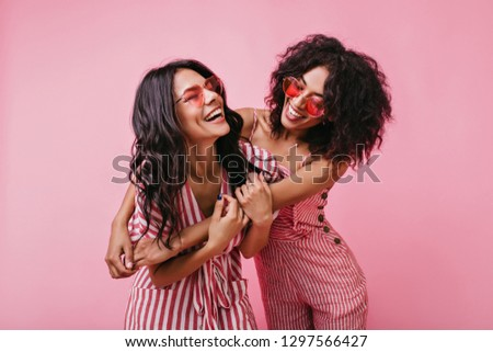 Romantic shot in cute studio of two tender young girls. Cheerful, naughty models with dark skin and curls rejoice excellent photo shoot