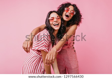 Emotional friends with beautiful tan, which emphasize light dresses, posing with sincere laugh on pink isolated background #1297566430