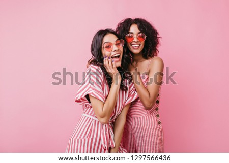 Cheerful, extraordinary girls in cute pink dresses are having fun. Studio shot on pretty ladies enjoying photo shoot #1297566436