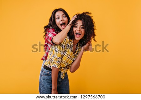 Crazy emotional girls are dabbling and having fun on orange background. Woman laughs and plays hair of her black girlfriend #1297566700