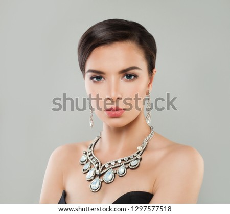 Elegant woman with short hairdo, makeup, luxurious diamond necklace and earrings portrait  #1297577518
