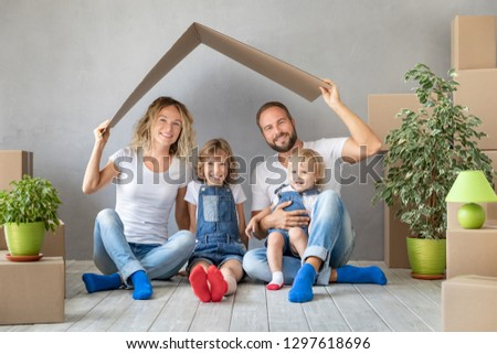Happy family with two kids playing into new home. Father, mother and children having fun together. Moving house day and real estate concept #1297618696