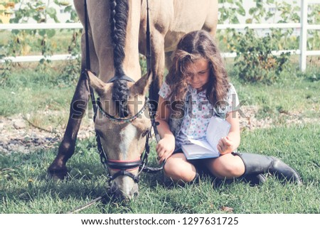 Сute girl is reading an interesting fantasy book in the fresh air with horse pony. Spring, summer, sunny. Concept of free time, dreams, interest, riding, hobby, reading a books, lessons, psyсholoпн #1297631725