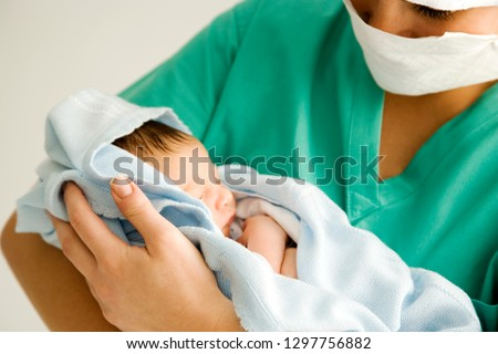 Maternity nurse wearing scrubs holding newborn baby wrapped in blanket #1297756882