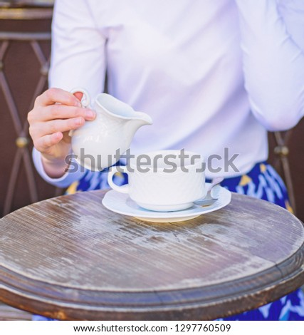 Coffee always better with milk. Hand female adding milk to black coffee outdoors cafe terrace, close up. Mug americano or black tea and jug with milk. Tips for healthier coffee drinking. #1297760509