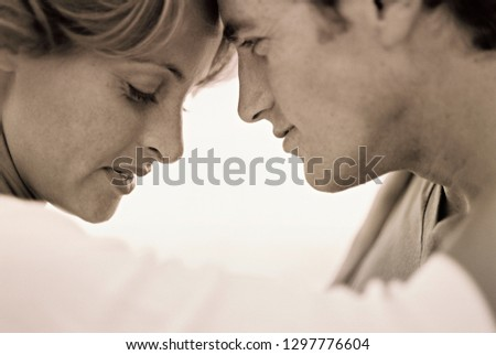 Monochrome shot of loving couple with heads touching #1297776604