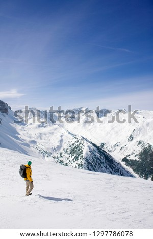 Man on winter vacation hiking through snowy mountain landscape #1297786078