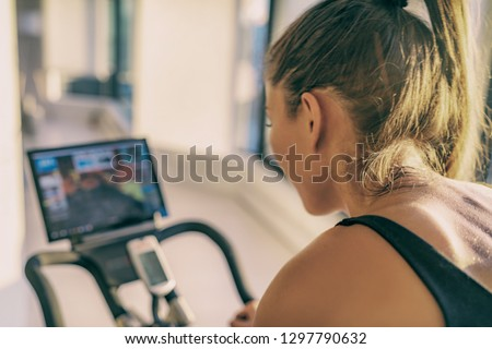 Smart fitness home workout biking screen with online classes woman training on stationary bike equipment indoors for biking exercise. Indoor cycling. Focus on the sweat on person's back. #1297790632