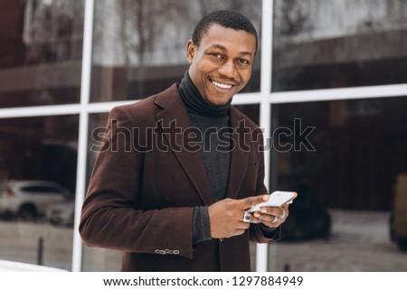 Portrait of handsome African - American businessman using smartphone in snowy winter city street near big office building, typing text message and looking at screen. #1297884949
