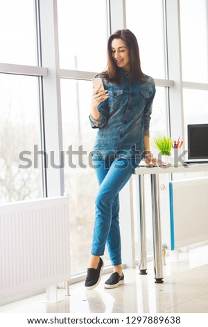 pretty designer looking woman with smartphone in office #1297889638