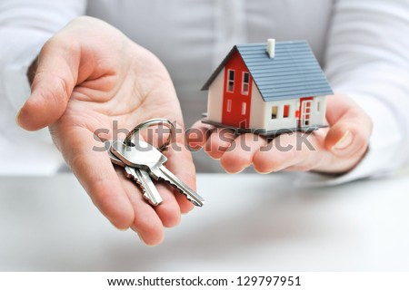 Real estate agent with house model and keys Royalty-Free Stock Photo #129797951