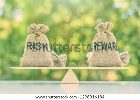 Risk reward ratio / risk management concept : Risk and reward bags on a basic balance scale in equal position, depicts investors use a risk reward ratio to compare the expected return of an investment #1298016184