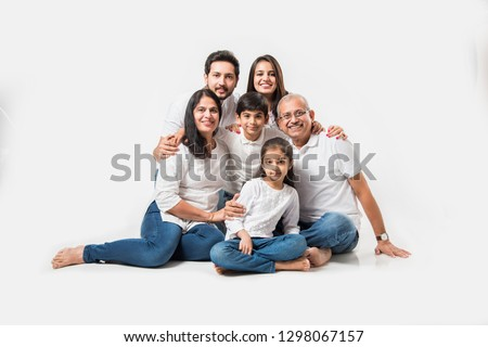 indian/asian family sitting over white background. senior and young couple with kids wearing white top and blue jeans. selective focus #1298067157