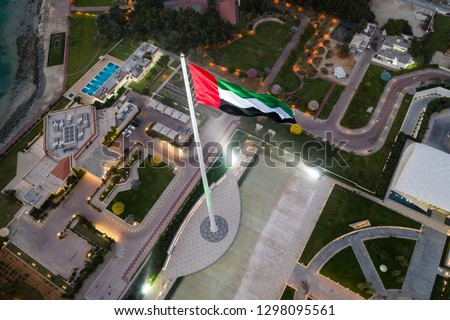 Unique aerial view of the United Arab Emirates flag waving at night.