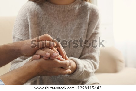 Man comforting woman on light background, closeup of hands. Help and support concept #1298115643