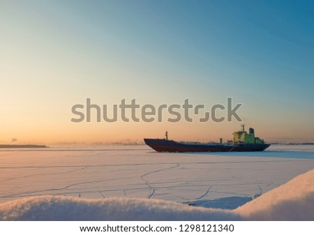 Arkhangelsk. Sunny winter day on the Bank of the Northern Dvina. January. Merchant ship in the ice on the fairway of the port of Arkhangelsk.  #1298121340