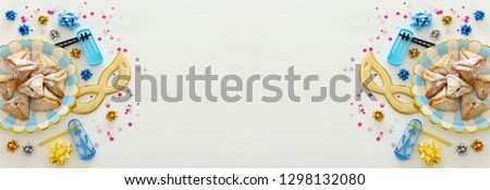 Purim celebration concept (jewish carnival holiday) over white wooden background. Top view, Flat lay #1298132080