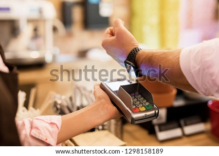 Person paying at cafe with smart watch wirelessly on POS terminal #1298158189