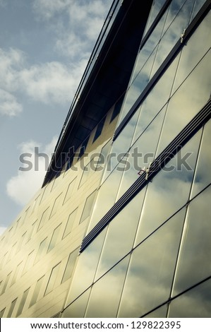 Reflection of the cloudy sky in a modern glass building #129822395