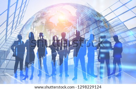 Silhouettes of business people working together over skyscraper background with double exposure of Earth and Forex graph. Toned image. Elements of this image furnished by NASA #1298229124