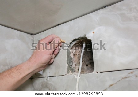 Man is installing the wall bathroom fan vent. Restoration process. Wires in hands. #1298265853