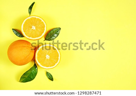 Close up image of juicy organic whole and halved oranges with green leaves & visible core texture, isolated yellow background, copy space. Macro shot of bright citrus fruit slices. Top view, flat lay. #1298287471