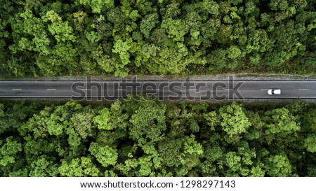 Aerial view road going through forest, Road through the green forest, Aerial top view car in forest, Texture of forest view from above, Ecosystem and healthy environment concepts and background. Royalty-Free Stock Photo #1298297143